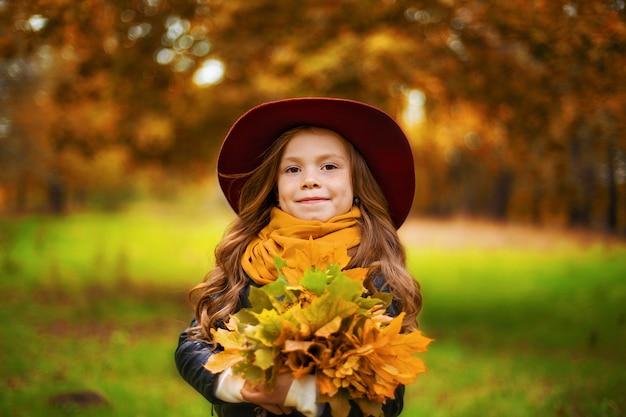 秋のカエデの花束を手に持っている笑顔の若い女の子の肖像画を残します。