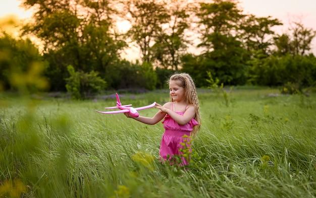 赤ちゃんは森と背の高い草の背景にピンクの飛行機を発射します。ピンクのスーツを着たピンクの飛行機で遊ぶ