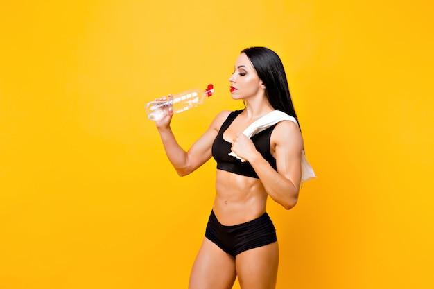筋肉の女性は休憩と飲料水を持っています