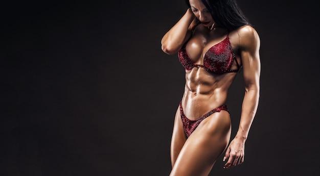 Спортивная сексуальная загорелая молодая девушка с большими мышцами живота