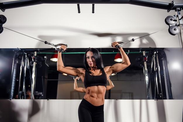 Женщина сгибая мышцы на фуникулере в спортзале