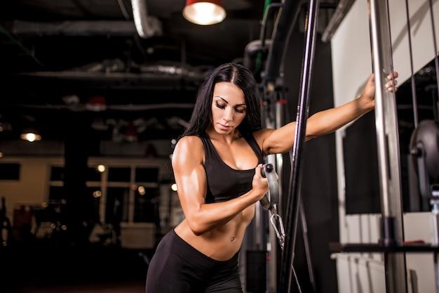 女性のジムでケーブルマシンの筋肉を屈曲