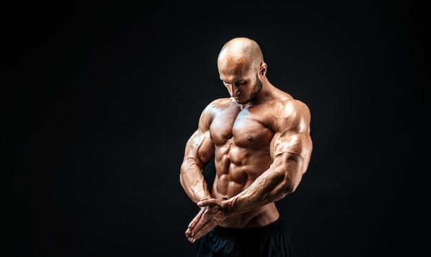 完璧な腹筋、肩、上腕二頭筋、上腕三頭筋、胸を持つ強力なボディービルダー男