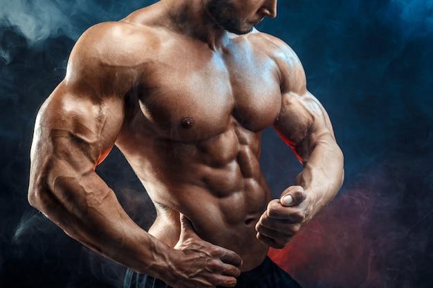 完璧な腹筋、肩、上腕二頭筋、上腕三頭筋、胸を持つ認識できない強いボディービルダー男