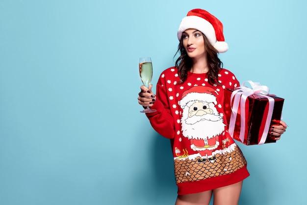 Симпатичная брюнетка женщина в красном свитере с санта, бокал шампанского на синем фоне