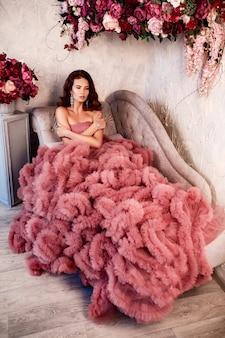 巻き毛の美しいブルネットの女性、ウェディングドレスでポーズをとって柔らかい化粧。