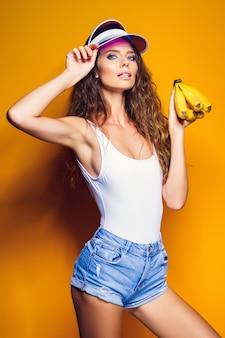 Женщина в купальнике и синие шорты, держа банан и позирует, изолированные на желтом фоне