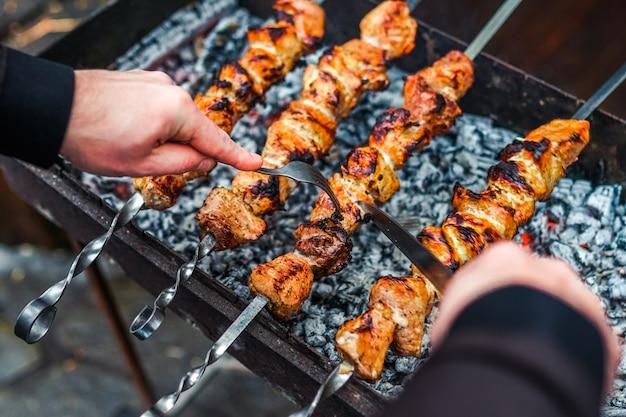 Приготовление на гриле шашлыка на металлическом вертеле. жареное мясо, приготовленное на гриле