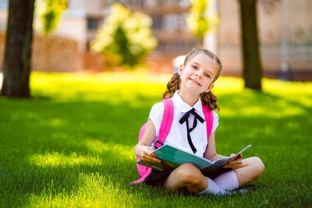 Маленькая школьница с розовым рюкзаком сидит на траве после уроков и читает книгу или изучает уроки,