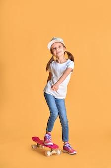 黄色の壁の上のスケートボードとカジュアルでスタイリッシュな小さな女の子子供女の子