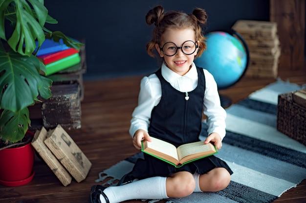 Умная девушка с учебником в школе