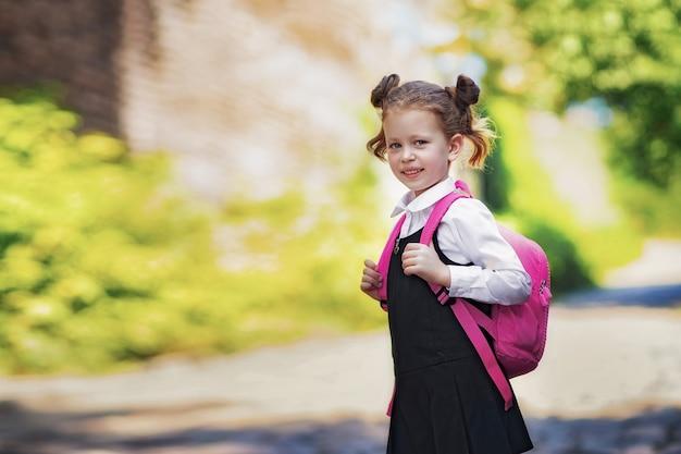 Улыбается девушка студента носить школьный рюкзак. портрет счастливой кавказской молодой девушки за пределами начальной школы. улыбаясь школьница, глядя на камеру.