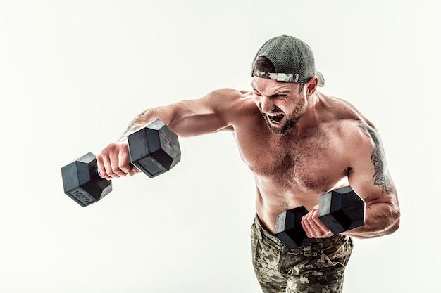 Мускулистый атлет культурист мужчина в камуфляжных штанах с голым торсом, пробивая гантелями, как боксер