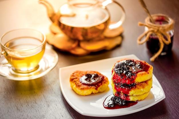 Сладкие сырники на белой тарелке с зеленым ромашковым чаем. выборочный фокус.