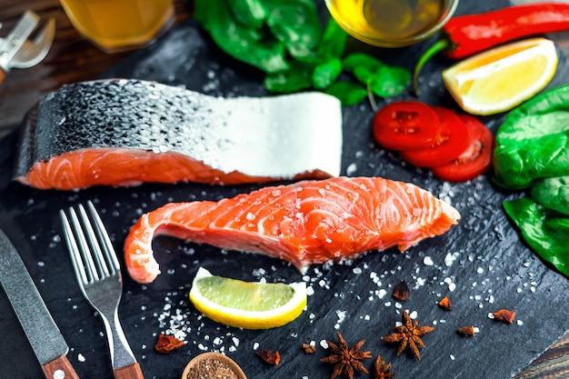 Сырые филе лосося и ингредиенты для приготовления пищи на темной стене.
