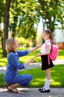 Первый день в школе. мама воспитывает маленького ребенка школьницей в первом классе
