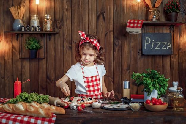 市松模様のエプロンでかわいい女の子が緑のピザとピザを振りかける