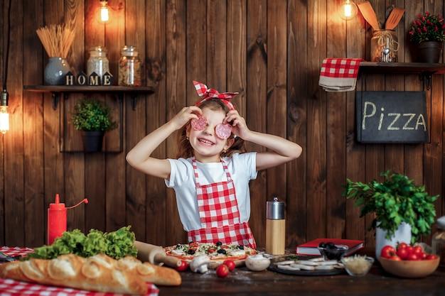Смешная девчонка готовит пиццу и дурачится с кусочками салями