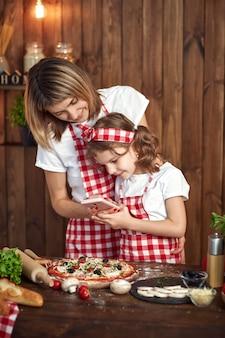 母と娘がスマートフォンで調理されたピザの写真を撮る