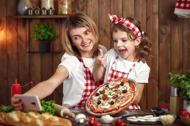 Мать и дочь, принимая селфи с пиццей на смартфоне