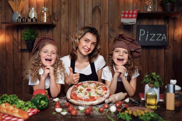 キッチンでピザを調理する娘を持つ母