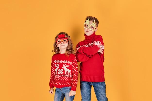 暖かい赤いクリスマスセーターの子供たち