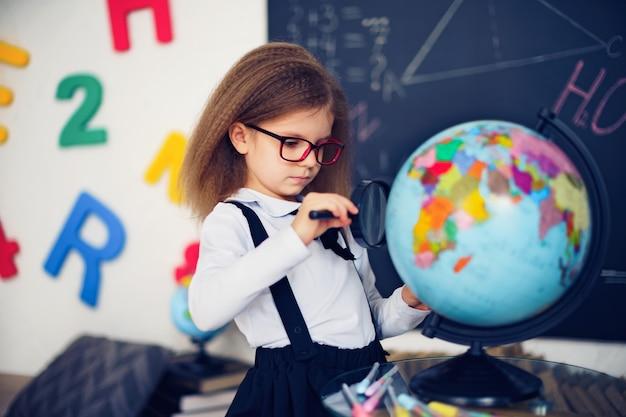 Портрет красивой молодой школьницы, исследующей земной шар через лупу.