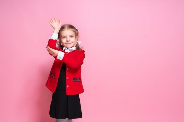 Смешная школьница в форме поднимая руку