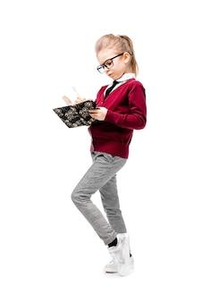 白いシャツと白い壁の近くに立って、モデルのようなポーズのグレーのパンツで美しい少女