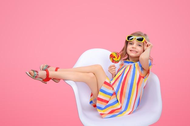 Милая девушка в солнечных очках с леденцом на палочке