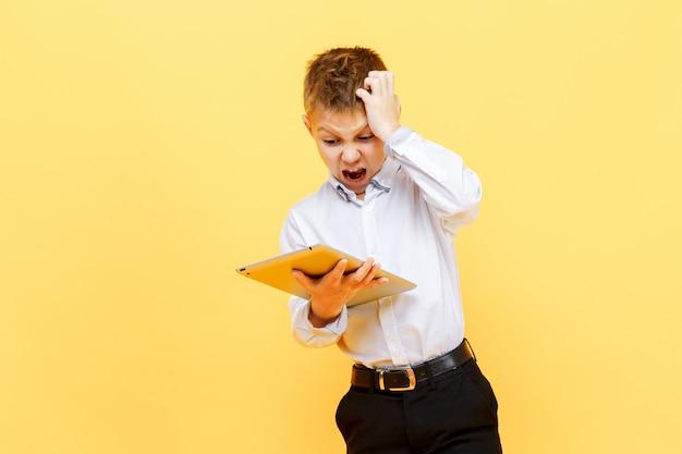 Яростный мальчик позирует с планшета