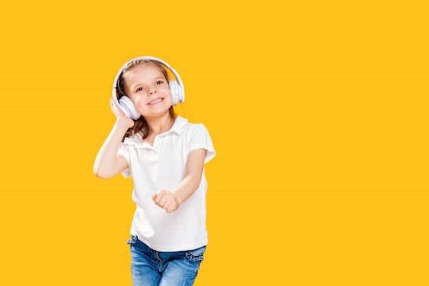 Девушка слушает музыку в беспроводных наушниках. танцовщица. счастливый маленькая девочка танцует под музыку. милый ребенок, наслаждаясь счастливой танцевальной музыки.