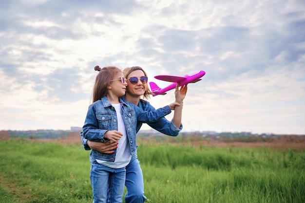 Мать и дочь играют с игрушечным самолетом