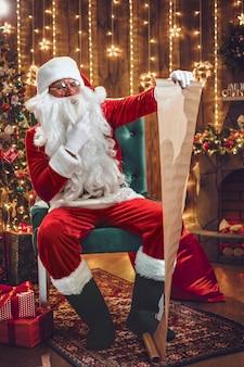 Портрет счастливого санта-клауса, сидящего в своей комнате дома возле елки и читающего рождественское письмо или список пожеланий