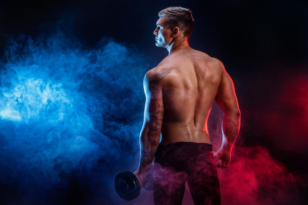 Крупный план культуриста человека красивой силы атлетического отдыхая пока стойка с гантелью. фитнес мускулистое тело на темном фоне дыма. идеальный мужчина. крутой культурист, тату, позирует.