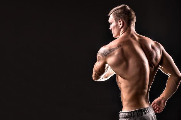 筋肉男のポーズ。背面図。黒い背景