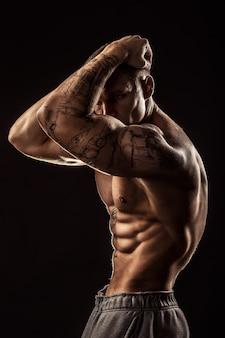 彼の頭を保持しているタトゥーの筋肉男。灰色の背景に分離