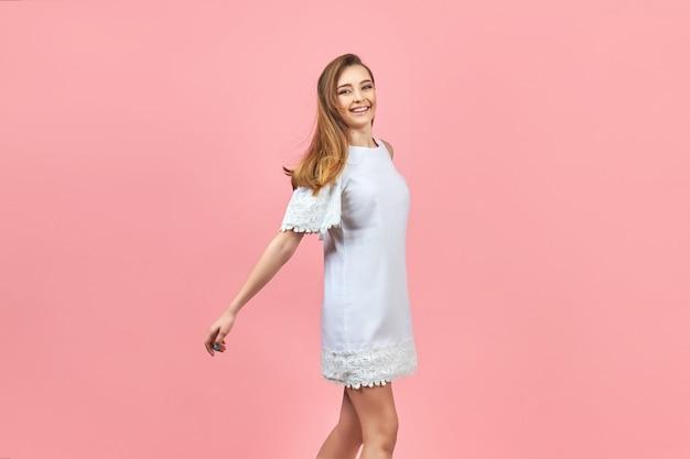 Красивая девушка в белом платье и позирует на розовом фоне.