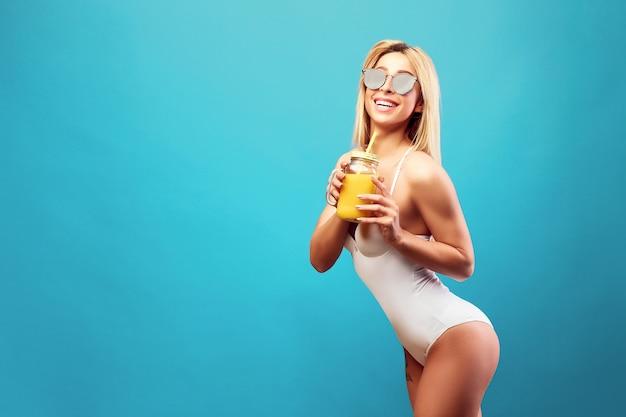 瓶の中のジュースとボディースーツの女性