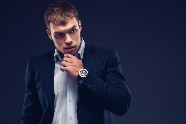 暗い背景にファッション青年実業家黒スーツ