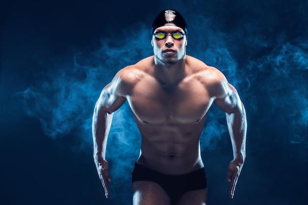 Привлекательный и мускулистый пловец. съемка студии молодого без рубашки спортсмена на черной предпосылке. человек в очках