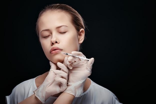 化粧品の注入を得る若い白人女性の肖像画