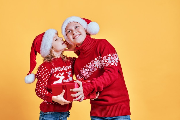 Милые дети с подарком в новогодних шапках