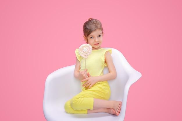 Довольная девушка с конфетой в кресле