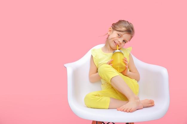 Мечтает молодая девушка с лимонадом на розовом