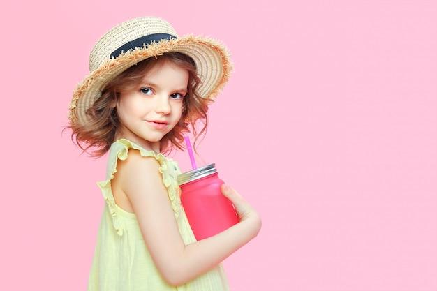 Стильная маленькая девочка с напитком на розовом