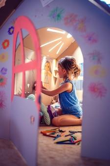 Очаровательная девушка играет в игрушечном домике
