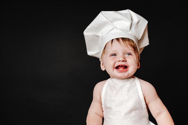 Очаровательный младенец в шляпе повара и фартуке
