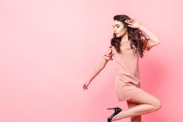 Красивая модная девушка с длинными вьющимися волосами в розовом платье в студии на розовом фоне.