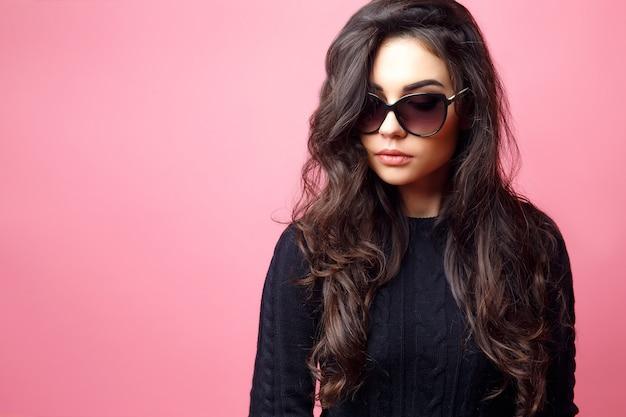 Молодая довольно сексуальная женщина или девушка с милым лицом и длинными темными волосами в темных очках и черном свитере позирует на розовом фоне